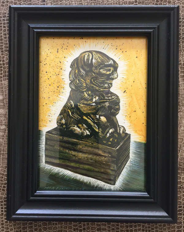 glowing foo dog with gold background rendered in scratchboard by Lori McAdams in a black frame against a snake skin background
