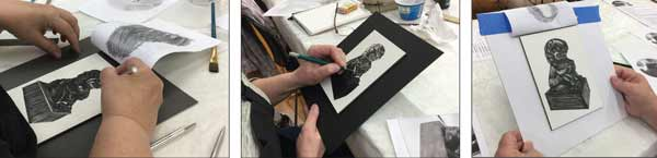 three artists each drawing a black and white foo dog in scratchboard.