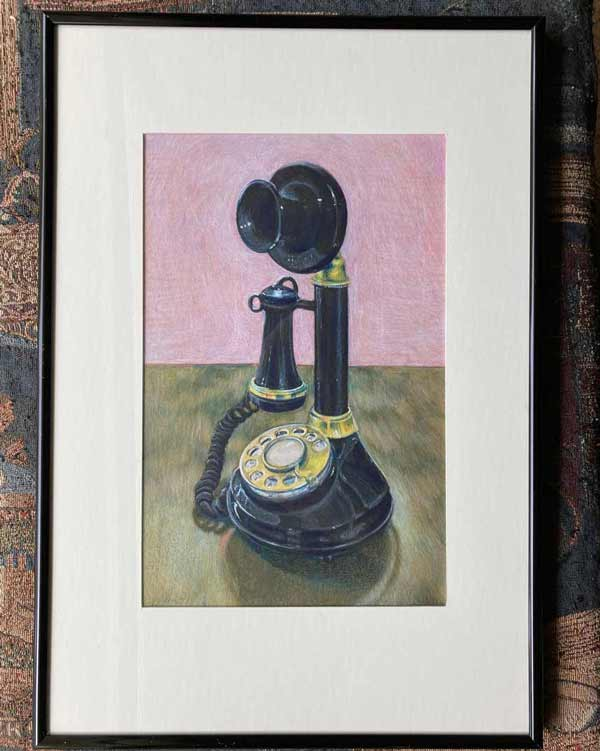 Framed drawing of a black old candlestick-style black rotary phone with golden dial and accents aginst a wooedn table and pink background.