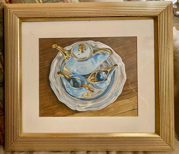 Gold framed drawing of a blue and gold blue porcelain teaset on a silver platter against a wooden table.
