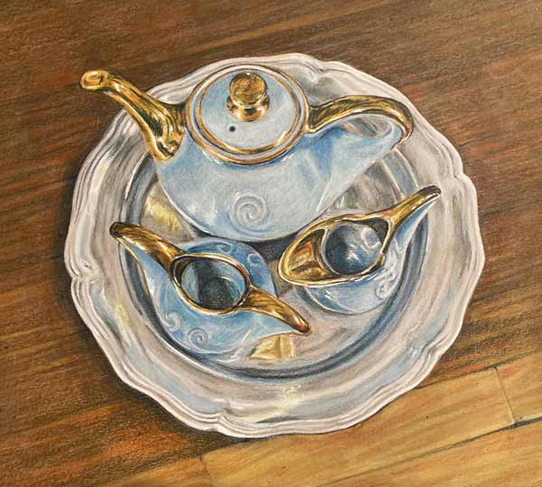 Blue and gold blue porcelain teaset on a silver platter against a wooden table.