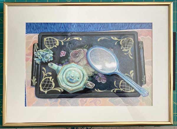 Black laquer tray with celedon teapot and flowers and blue lucite mirror on a pale floral place mat in golden strip frame.