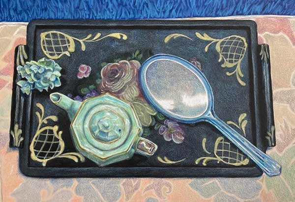 Black laquer tray with celedon teapot and flowers and blue lucite mirror on a pale floral place mat.